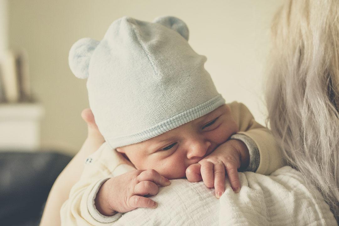 Bebé lactante descansa en el hombro de su madre