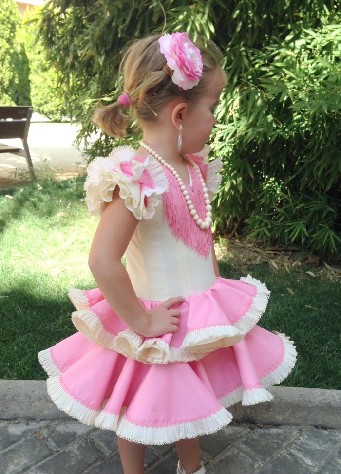 Traje de gitana niña en popelín beige, con dos volantes dobles, combinados con volantes en color rosa. Los adornos esta compuesto de plisados en color beige.