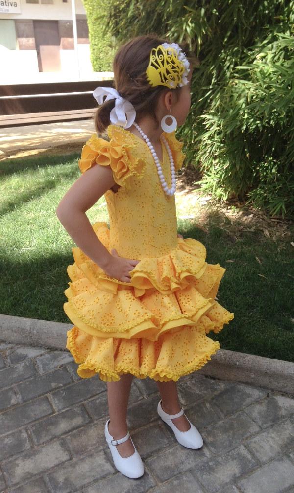 Traje de gitana niña en amarillo y compuesto de dos volantes dobles. El cuerpo del traje y el volante es tela perforada amarilla, y el doble volante es popelín amarillo adornado con encaje fruncido en color amarillo.
